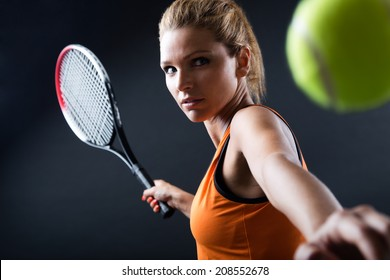 Portrait of beautiful woman playing tennis indoor. Isolated on black.