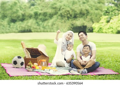 Portrait of beautiful woman pointing to something while picnicking with her family in the park