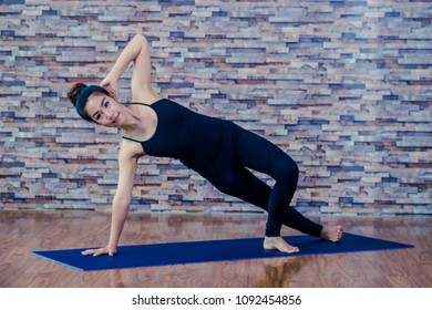 Portrait of a beautiful woman practicing yoga in a studio.