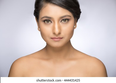 Portrait of beautiful woman with pretty face with clean skin on grey background