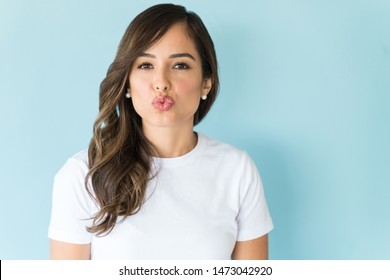 Portrait of beautiful woman puckering lips on colored background