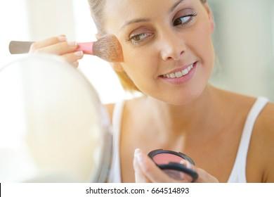 Portrait of beautiful woman putting makeup on