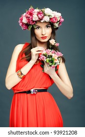 Portrait of beautiful woman in red  dress with a crown on his head and a bunch of flowers on a dark background in the studio. The concept of friendly spring.