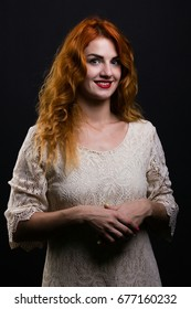 portrait of beautiful woman with red hair and green eyes posing in studio