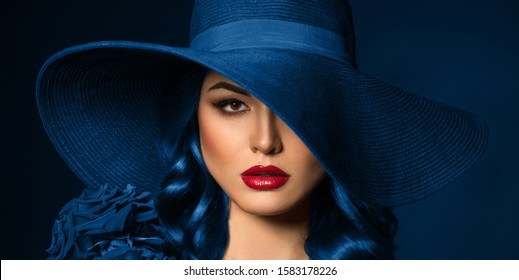 Portrait of a beautiful woman with red lips in a hat, toned in color of the year 2020, classic blue. - Shutterstock ID 1583178226