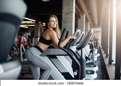 Portrait of beautiful woman running on elliptical cross trainer or orbitrek warming up her body before a long workout session.