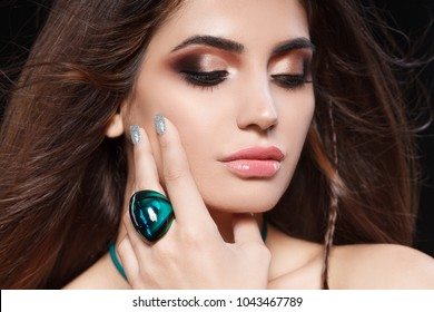 Portrait of beautiful woman with sensitive sexy view, silver glitter nails design and jewelery with natural stones