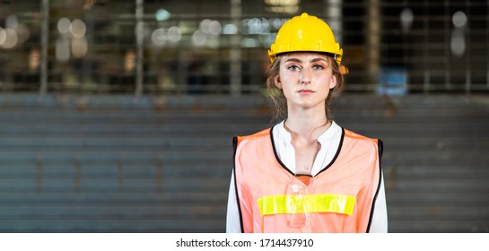 Portrait of beautiful woman serious civil engineer wearing uniform and hardhats working at industrial factory. Engineering and architecture concept