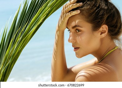 Portrait of beautiful woman with shadows of palm leaf on her face