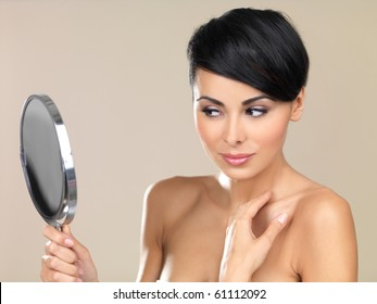 Portrait of beautiful woman, she is looking at the mirror
