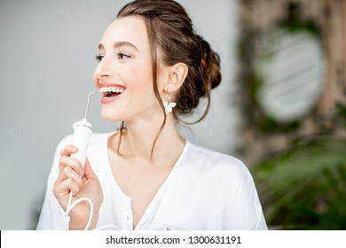 Portrait of a beautiful woman with shiny smile holding irrigator tool for teeth cleaning in the bathroom