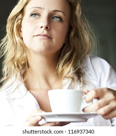 Portrait of beautiful woman, sitting in a cafe outdoor, drinking coffee