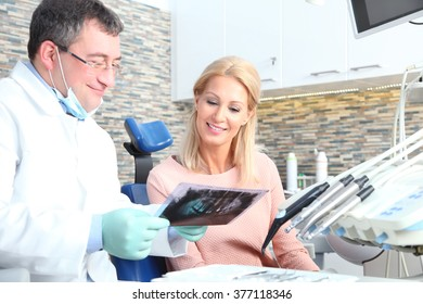 Portrait of beautiful woman sitting at dentist and consulting with male doctor while checking x-ray.