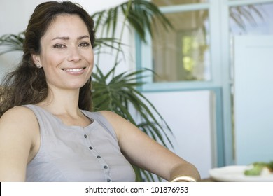 Portrait of a beautiful woman sitting at home with plants and smiling at camera.