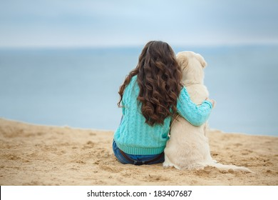 Portrait of a beautiful woman sitting on the sea shore with a playful young dog, Nature