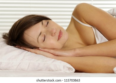 portrait of a beautiful woman sleeping in bed on a light background