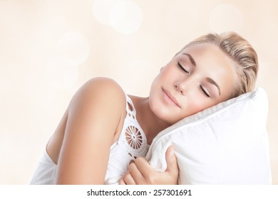 Portrait of beautiful woman sleeping on the pillow isolated on blur beige background, happy calm day dreaming, conception of relaxation