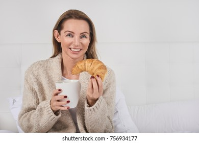 Portrait of a beautiful woman smiling while having breakfast in bed with a cup of coffee or milk and a delicious French croissant