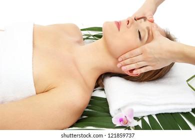 Portrait of beautiful woman in spa salon taking head massage