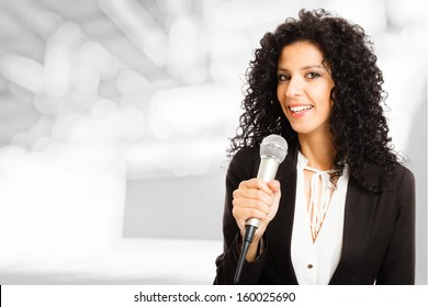 Portrait of a beautiful woman speaking in a microphone