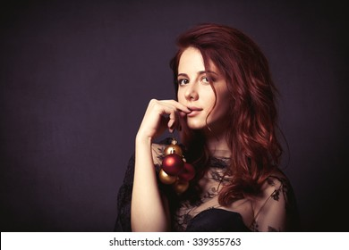 Portrait of a beautiful woman in style dress with christmas baubles on dark background