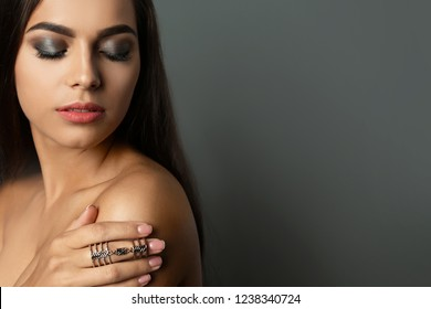 Portrait of beautiful woman with stylish makeup on gray background. Space for text