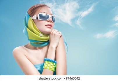 a portrait of a beautiful woman in sunglasses against blue sky