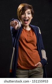 Portrait of a beautiful woman with a surprised face and pointing to the camera, over a dark background