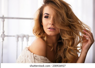Portrait of beautiful woman in sweater on bed