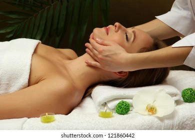 Portrait of beautiful woman taking head massage on green background
