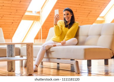 Portrait of a beautiful woman taking a selfie photo her the phone while relaxing on the sofa in a wooden attic loft.
