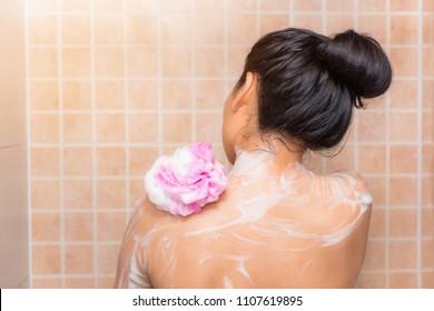 Portrait of beautiful woman taking shower with bath sponge., Health skincare concept.