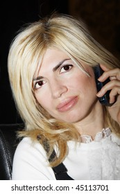 Portrait of the beautiful woman talking by a mobile phone