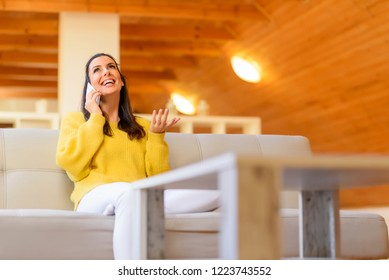 Portrait of a beautiful woman talking on the phone while relaxing on the sofa in a wooden attic loft.
