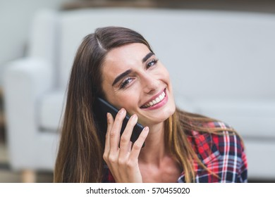 Portrait of beautiful woman talking on the phone at home