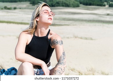 Portrait of a beautiful woman with a tattoo in sun glasses under the sunlight