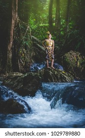 Portrait of Beautiful woman in Thai Traditional dress, Kinnara In Buddhist mythology, enjoy outdoor at forest with water fall