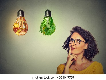 Portrait beautiful woman thinking looking up at junk food and green vegetables shaped as light bulb isolated on gray background. Diet choice right nutrition healthy lifestyle wellness concept