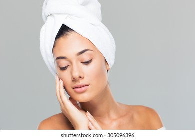 Portrait of a beautiful woman with towel on head on gray background