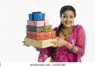 Portrait of a beautiful woman in traditional dress holding gifts and smiling
