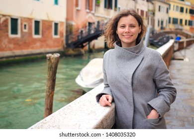 Portrait of beautiful woman in Venice, Italy. Girl posing on venetian canal. Weekend in Venezia. Woman tourist in Venice