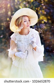 portrait of beautiful woman in victorian age dress and fancy hat walking outdoor