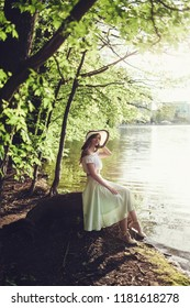 Portrait of a beautiful woman in a vintage dress and hat sitting in park. Pretty tenderness model near lake.