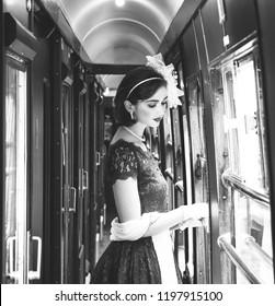 Portrait of beautiful woman in vintage tea dress standing in corridor of locomotive train