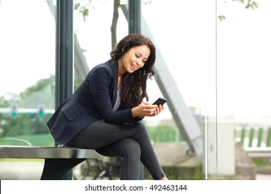 Portrait of beautiful woman waiting at bus stop with smart phone