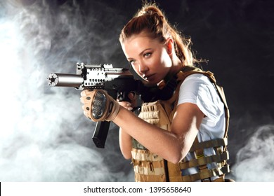 Portrait of a beautiful woman warrior in military outfit with firearm in hands, aiming at enemy, fighting in smoke from exploding shells at night
