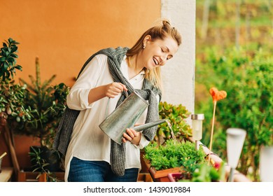 Portrait of beautiful woman watering green plants on the balcony, small cozy garden in apartment
