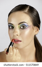 Portrait of beautiful woman wearing colorful graphic makeup applying lipstick.