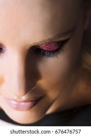 Portrait of beautiful woman wearing edgy makeup with purple sparkle eyeshadow  and dark eyeliner.