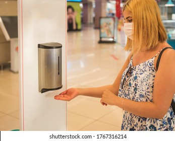 Portrait of beautiful woman wearing protective face mask uses automatic hand sanitizer dispenser at the entrance of shopping center during covid-19 outbreak .